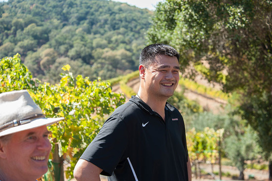 Image: Yao Ming in the vineyards of one of his Cabernet Sauvignon growers with Jay Bemke, a board member for Yao Family Wines. Credit: Avis Mandel, for Yao Family Wines